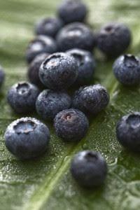 Group of blueberries on banana leaf.